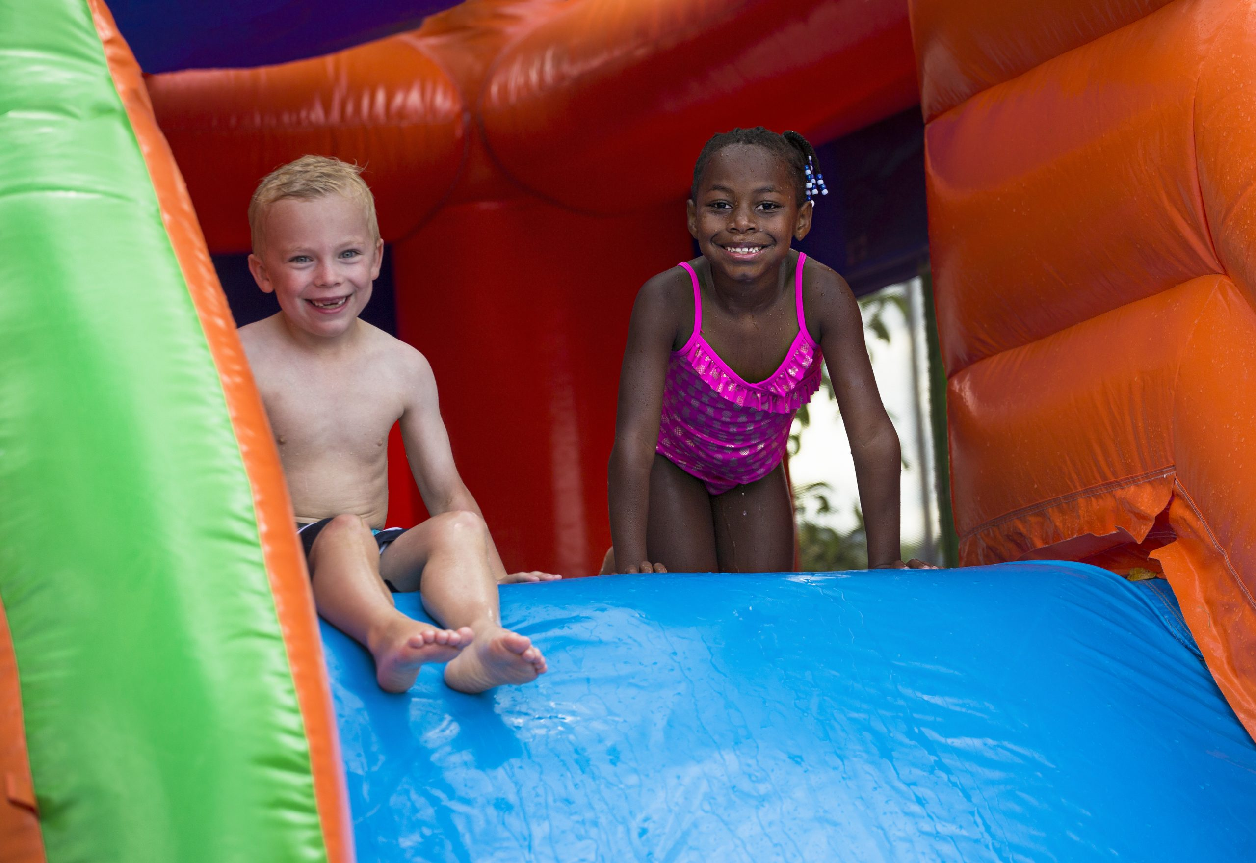 Happy kids sliding down an inflatable bounce house